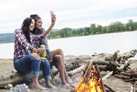 Female friends taking selfie while sitting on tree trunk by campfire against river 11100064454| 写真素材・ストックフォト・画像・イラスト素材|アマナイメージズ
