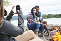 Woman photographing happy female friends sitting on tree trunk by campfire against river 11100064455| 写真素材・ストックフォト・画像・イラスト素材|アマナイメージズ
