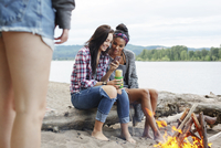 Female friends using smart phone while sitting on tree trunk by campfire against river 11100064456| 写真素材・ストックフォト・画像・イラスト素材|アマナイメージズ
