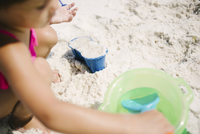 High angle view of girl playing with toys and sand at beach during sunny day 11100064735| 写真素材・ストックフォト・画像・イラスト素材|アマナイメージズ