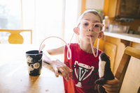 Portrait of boy drinking juice through straw glasses while holding stuffed toy at home 11100064745| 写真素材・ストックフォト・画像・イラスト素材|アマナイメージズ