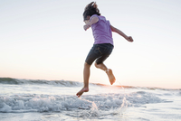 Low angle view of girl jumping on waves at beach against clear sky during sunset 11100064870| 写真素材・ストックフォト・画像・イラスト素材|アマナイメージズ