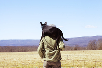 Rear view of man carrying dog on shoulders while standing at field against blue sky 11100065759| 写真素材・ストックフォト・画像・イラスト素材|アマナイメージズ