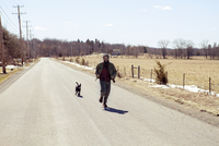 Full length of man and dog running on country road during vacation 11100065765| 写真素材・ストックフォト・画像・イラスト素材|アマナイメージズ