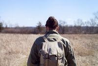 Rear view of male hiker carrying backpack while standing at field during sunny day 11100065775| 写真素材・ストックフォト・画像・イラスト素材|アマナイメージズ