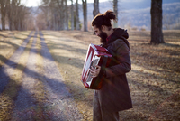 Side view of male hipster playing accordion at field during vacation 11100065784| 写真素材・ストックフォト・画像・イラスト素材|アマナイメージズ