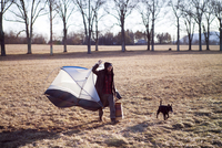 Full length of man carrying portable tent while walking with dog on field 11100065787| 写真素材・ストックフォト・画像・イラスト素材|アマナイメージズ