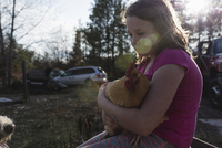 Close-up of sad girl holding chicken while sitting in lawn 11100065906| 写真素材・ストックフォト・画像・イラスト素材|アマナイメージズ