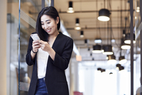 Happy businesswoman looking at smart phone while standing in office 11100066152| 写真素材・ストックフォト・画像・イラスト素材|アマナイメージズ