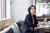 Portrait of confident businesswoman sitting at table in office 11100066166| 写真素材・ストックフォト・画像・イラスト素材|アマナイメージズ