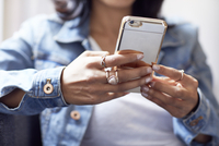Cropped hands of businesswoman holding smart phone in office