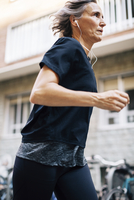 Low angle view of woman jogging while listening music 11100066608| 写真素材・ストックフォト・画像・イラスト素材|アマナイメージズ