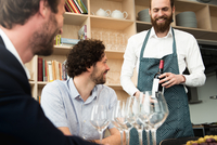Bartender holding wine bottle while standing by customers at table in tasting room 11100067516| 写真素材・ストックフォト・画像・イラスト素材|アマナイメージズ