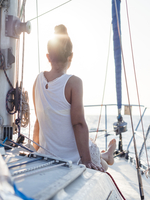 Rear view of woman sitting in sailboat against clear sky 11100067662| 写真素材・ストックフォト・画像・イラスト素材|アマナイメージズ