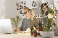 Businesswoman using laptop while sitting at desk by houseplants in creative office 11100068594| 写真素材・ストックフォト・画像・イラスト素材|アマナイメージズ