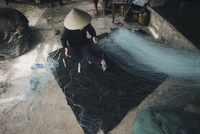 High angle view of person in conical hat repairing fishing net 11100068650| 写真素材・ストックフォト・画像・イラスト素材|アマナイメージズ