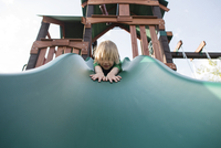 Low angle portrait of playful girl sliding on slide at playground