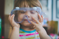 Close-up of playful girl wearing swimming goggles at home