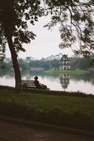 Rear view of woman looking at view while sitting on bench at Hoan Kiem Lake 11100069199| 写真素材・ストックフォト・画像・イラスト素材|アマナイメージズ