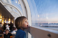 Side view of girl looking through window while traveling in cruise ship 11100069628| 写真素材・ストックフォト・画像・イラスト素材|アマナイメージズ