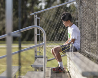 Thoughtful teenage boy sitting on bench against chainlink fence at playing field 11100069673| 写真素材・ストックフォト・画像・イラスト素材|アマナイメージズ