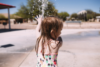 Playful girl playing with water in park during summer 11100069832| 写真素材・ストックフォト・画像・イラスト素材|アマナイメージズ