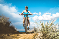 Low angle view of cyclist riding mountain bike on dirt trail against cloudy sky 11100069855| 写真素材・ストックフォト・画像・イラスト素材|アマナイメージズ