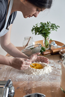 High angle view of woman mixing egg in pasta flour on kitchen island 11100070427| 写真素材・ストックフォト・画像・イラスト素材|アマナイメージズ