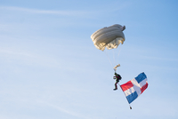 Low angle view of paraglider paragliding with flag against sky 11100070567| 写真素材・ストックフォト・画像・イラスト素材|アマナイメージズ