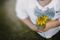 Midsection of boy holding sunflower while standing on field 11100070950| 写真素材・ストックフォト・画像・イラスト素材|アマナイメージズ