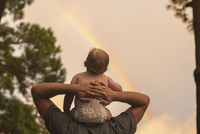 Rear view father carrying son on shoulders while looking at rainbow 11100070965| 写真素材・ストックフォト・画像・イラスト素材|アマナイメージズ