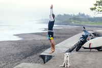 Full length of man stretching while standing on retaining wall by dog at beach 11100071441| 写真素材・ストックフォト・画像・イラスト素材|アマナイメージズ