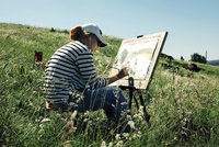 Woman painting while listening music on grassy field during sunny day 11100071601| 写真素材・ストックフォト・画像・イラスト素材|アマナイメージズ