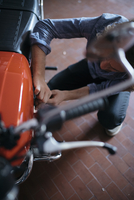 High angle view of man repairing his motorcycle at workshop 11100072386| 写真素材・ストックフォト・画像・イラスト素材|アマナイメージズ