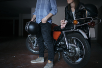 Low section of young couple standing by motorcycle at auto repair shop 11100072393| 写真素材・ストックフォト・画像・イラスト素材|アマナイメージズ