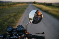 Reflection of young couple on motorcycle seen in side-view mirror 11100072395| 写真素材・ストックフォト・画像・イラスト素材|アマナイメージズ