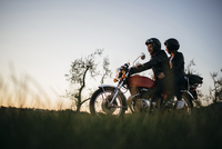 Low angle view of young couple on motorcycle against clear sky 11100072396| 写真素材・ストックフォト・画像・イラスト素材|アマナイメージズ