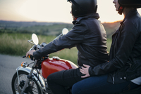 Side view of young couple on motorcycle 11100072399| 写真素材・ストックフォト・画像・イラスト素材|アマナイメージズ