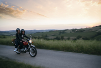 Young couple riding on motorcycle at country road during sunset 11100072400| 写真素材・ストックフォト・画像・イラスト素材|アマナイメージズ