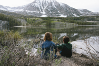Rear view of siblings looking at view while sitting by lake at Inyo National Forest 11100072579| 写真素材・ストックフォト・画像・イラスト素材|アマナイメージズ