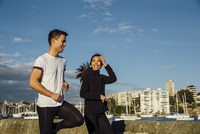 Happy young couple exercising on promenade against sky in city 11100072740| 写真素材・ストックフォト・画像・イラスト素材|アマナイメージズ