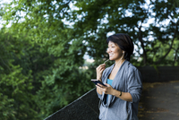Happy woman talking on smart phone while using earphones on footpath against branches 11100072925| 写真素材・ストックフォト・画像・イラスト素材|アマナイメージズ