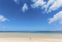 Rear view of baby girl sitting on sand at beach against sky 11100073217| 写真素材・ストックフォト・画像・イラスト素材|アマナイメージズ