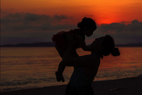 Silhouette mother playing with daughter while standing on shore at beach against sky during sunset 11100073266| 写真素材・ストックフォト・画像・イラスト素材|アマナイメージズ