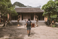 Rear view of tourist with backpack walking towards pagoda 11100073377| 写真素材・ストックフォト・画像・イラスト素材|アマナイメージズ