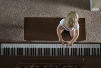 Overhead view of boy playing piano at home 11100073758| 写真素材・ストックフォト・画像・イラスト素材|アマナイメージズ