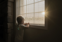 Boy playing with window blinds while standing at home 11100073765| 写真素材・ストックフォト・画像・イラスト素材|アマナイメージズ