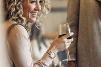 Cheerful businesswoman holding wineglass while looking away in hotel 11100073813| 写真素材・ストックフォト・画像・イラスト素材|アマナイメージズ