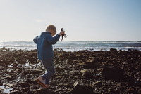 Boy holding toy animal while walking on shore against sea and sky 11100074096| 写真素材・ストックフォト・画像・イラスト素材|アマナイメージズ