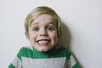 Close-up portrait of boy clenching teeth against wall at home 11100074114| 写真素材・ストックフォト・画像・イラスト素材|アマナイメージズ